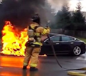 A screenshot from a YouTube video shows a Tesla Model S on fire as a result of a battery fire.