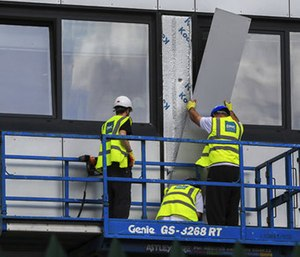 Workers remove cladding from Whitebeam Court, in Pendleton, Manchester, Monday June 26, 2017. The list of high-rise apartment towers in Britain that have failed fire safety tests grew to 60, officials said Sunday, revealing the mounting challenge the government faces in the aftermath of London's Grenfell Tower fire tragedy.