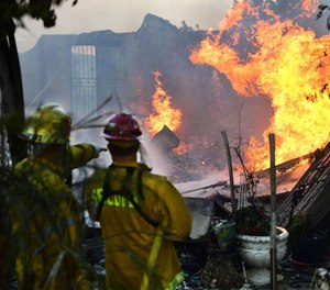 Firefighters put out flames still burning from the South Fire which swept through Lytle Creek, California near Cajon Pass on August 25, 2021 damaging at least six homes and threatening a hundred.