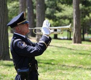 Officer Jeff Stagg plays a bugle for the Honor Guard.