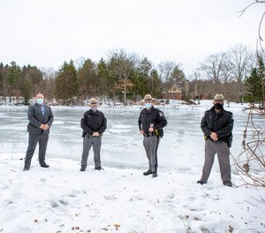 State troopers pose in front of an icy pond after rescuing a fisherman in Wayland, New York.
