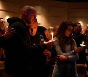 Elizabeth police officer Sean Bigler, middle, gets a hug from a fellow officer during a candle light vigil for their friend and fellow officer Douglas County deputy Zackari Parrish at Mission Hills Church in Littleton, Colo., Monday, Jan. 1, 2018.