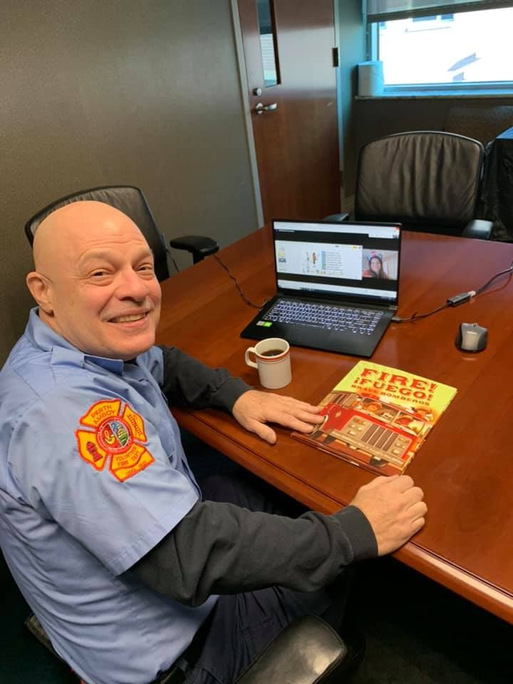 Perth Amboy Firefighter RL Anderson, a retired principal, prepares to read to students for Read Across America Day.
