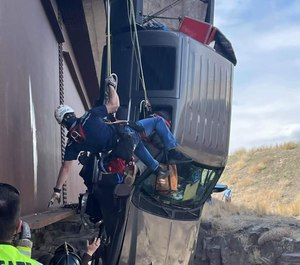 This image shows the scene where authorities say a set of camp trailer safety chains and quick, careful work by emergency crews saved two people after their pickup truck plunged off a bridge, leaving them dangling above a deep gorge in southern Idaho on Monday, March 15, 2021.