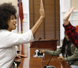 Mariah Parker, an Athens-Clarke County commissioner in Georgia, high-fives a high school student after a series of mock debates and votes inside the chamber at City Hall. The Georgia legislature approved legislation that would preempt the commission's powers, after the panel moved toward restricting police funding. State preemption of local powers is increasing nationwide.