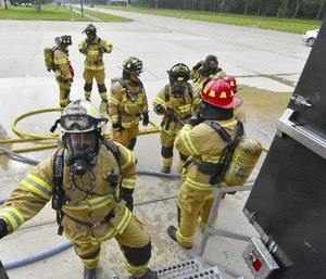 Arnold Air Force Base paramedic/firefighters prepare to enter the Kentucky Fire Commission mobile live fire rescue simulation training structure on May 11. Forty-one base firefighters, participated in the annual training experiencing high temperatures and smoke, and practicing firefighting and self-rescue techniques.