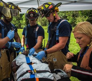 Firefighters and paramedics work together to secure a patient during an aircraft mishap exercise.