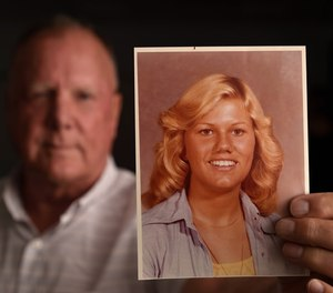 Jack Fleischli holds a photo of his sister, Ginger, when she 17. She was murdered at age 20.