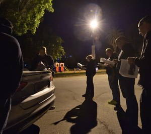 Officers from Fontana PD's child exploitation team gather at Elmer Digneo Park in Loma Linda at 4:30 a.m. to coordinate before serving a search warrant at the home of a person suspected of collecting and distributing images of child pornography.