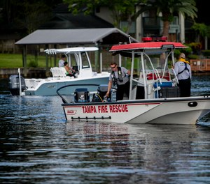 Fire Department rescue team operates a boat in the Hillsborough River near West Columbus Drive in Tampa on Thursday, August 2, 2018.