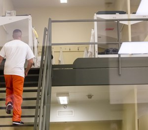 A detainee walks up to his bunk in one of the pods at Northwest ICE Processing Center in Tacoma.
