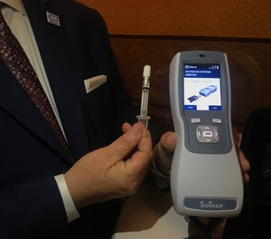 Fred Delfino, a law enforcement liaison with Abbott Toxicology, exhibits the saliva collection device being used by Michigan police to conduct roadside tests for drugged driving.