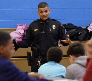 Erie Bureau of Police Sgt. Tom Lenox talks with students during a Police Athletic League after-school program. Speaking with police officers is one of the best things you can do to prepare yourself for a future career in law enforcement.