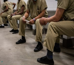 Detainees wait in the intake area before entering to Cermak Health Services for a COVID-19 test and health screening in the Cook County Jail.