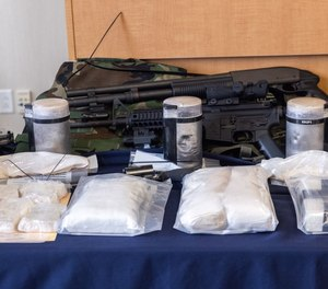 Packets of seized heroin, cocaine, fentanyl and firearms were on display as Hampden District Attorney Anthony Gulluni held a press conference on Wednesday to describe multi-agency efforts to dismantle a major drug trafficking organization.