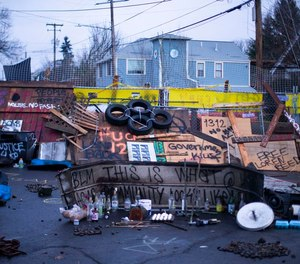 Signs and barricades remain outside a house on North Mississippi Ave. in Portland on December 9, 2020.