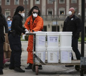 Stateville Correctional Center personnel pull carts of hand sanitizer and bars of soap on April 24, 2020.