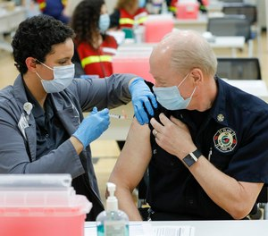Franklin County assistant health commissioner Alexandria Jones gives a COVID-19 vaccine to New Albany Plain Township fire chief Jack Rupp on Monday, Dec. 28, 2020.