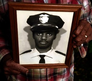 Nate Howard holds a photograph of Wallie Howard Jr. taken after Wally became a police officer. Howard is Wallie's uncle.