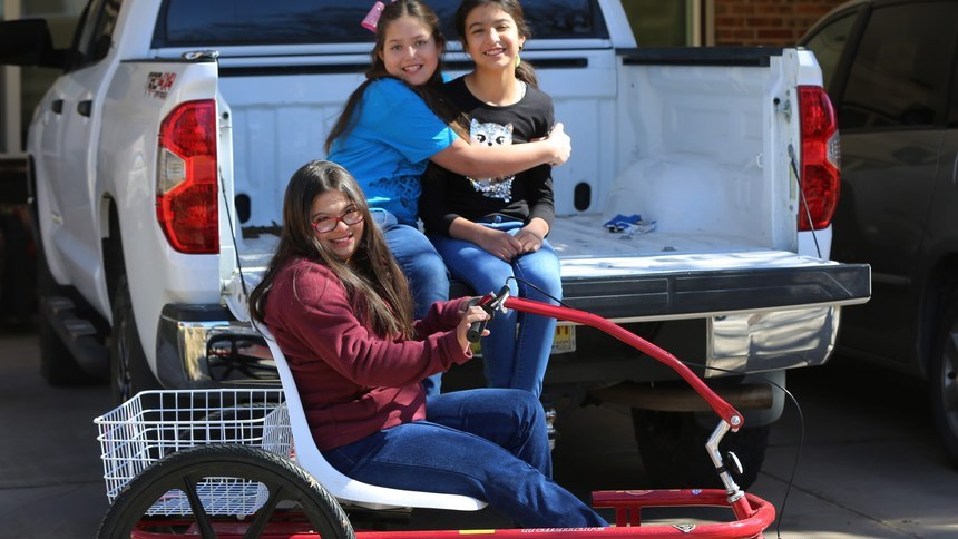 Middle School student Grace Holguin, 14, on her special needs trike, and her sisters Eve, 9, and Sophia, 10, picturedFriday, Feb. 19, 2021. (Bethany Freudenthal/Sun-News)