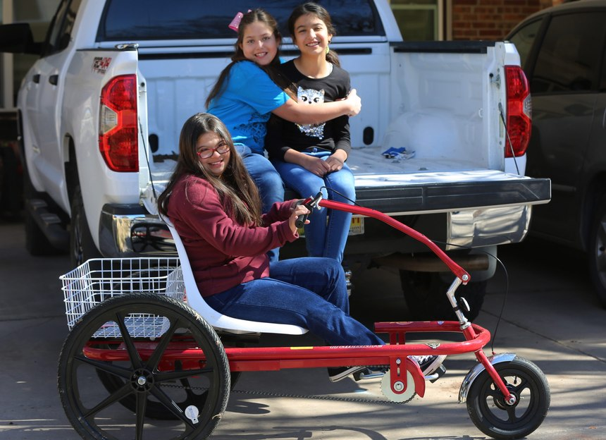 Middle School student Grace Holguin, 14, on her special needs trike, and her sisters Eve, 9, and Sophia, 10, picturedFriday, Feb. 19, 2021.