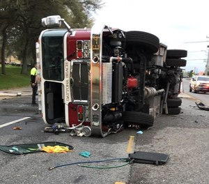 Police say a fire apparatus was flipped to its side when it was rear-ended by another vehicle Saturday. Five firefighters were injured and the driver of the other vehicle was killed.