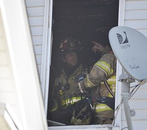 Firefighters work at the scene of an apartment fire in Ware, Mass. on Tuesday, March 23. North Brookfield Fire Chief Joseph Holway spotted the fire while off duty and evacuated residents.
