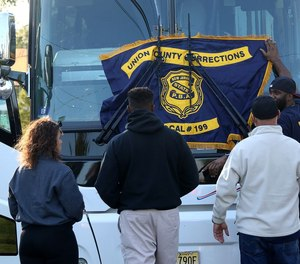 Members from PBA Local 199 Union County Corrections hang their banner on the front of a bus at a rally for COs in nearby Cumberland County, who were facing a similar proposal, with accompanying layoffs, last year.
