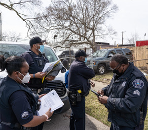 (Clockwise left to right) Detroit Police Department Neighborhood Police Officers Marcia Williams, Dan Robinson and Eric Hill gather with Sergeant Charles Spruce before handing out gun safety information and gun locks while going door-to-door along Fenelon Street on Detroit's east side on Thursday, March 25, 2021.