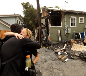 Courtney Gillenwater, facing, receives a hug of support from Brian Averill, with Venice Boardwalk Action Committee, in front of her fire damaged home. The fire is under investigation but residents in the neighborhood believe it may have been set by new homeless in the area.