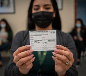 Receptionist Maribel Hidalgo displays her vaccination card after receiving the Moderna COVID-19 vaccine at the Virginia Garcia Memorial Health Center in Hillsboro, Oregon, on January 8, 2021.