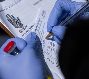A registered nurse works on filling out vaccine cards while holding a vial of the Moderna COVID-19 vaccine.