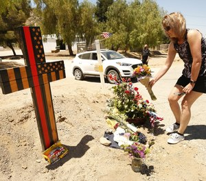Cindee Erdman places flowers at a memorial featuring a cross made of wood along with flowers located outside Los Angeles County Fire Dept. Station 81 where LA County Firefighter specialist Tory Carlon was killed in a shooting.