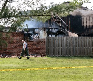 A firefighter walks by three destroyed town homes in the 400 block of Cardin Place in Eagleville on Thursday. Investigators say the blaze started inside one of the homes shortly before 1 p.m.