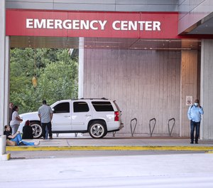 A group of people waits outside of Dell Seton Medical Center waiting for news about victims after a man shot and wounded 14 people at about 1:30 a.m. at the 400 block of 6th street in Austin, Texas on June 12, 2021.