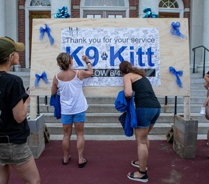 People gather and write messages of support at the Shine Braintree Blue event at the Braintree Town Hall on Monday, June 7, 2021, for the police officers who were shot and the K-9, Kitt, who was killed responding to a domestic call.
