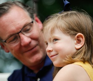Father Matt Uber holds his daughter Vera while he is interviewed about her cardiac arrest on Thursday, June 25, 2021, at their family home in Indiana. Uber was able to remember some CPR after watching an iconic CPR episode of the office and other programs, helping to save her life.