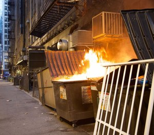 A dumpster fire burns on North Garland Court in the Loop on Sunday night, July 4, 2021.