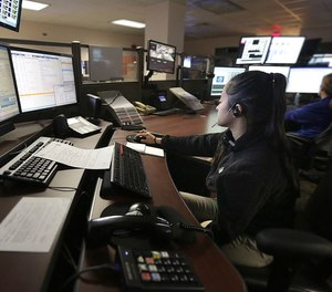 At the Newport News 911 call center, dispatchers give assistance and work at a number of monitors.