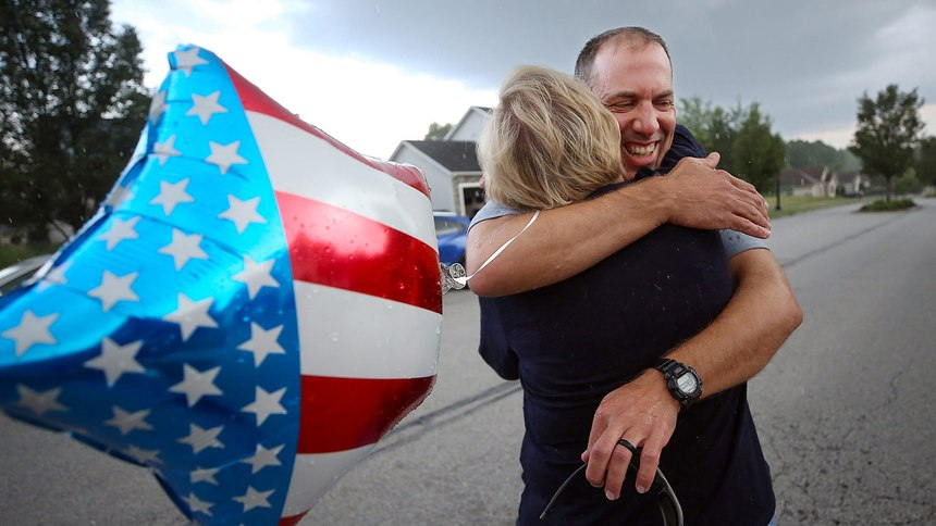 Andy Miller of Ohio Task Force 1 hugs his wife, Jenna Bates, Thursday night when he returned home to Cuyahoga Falls after assisting with recovery efforts at the deadly Florida condo collapse.
