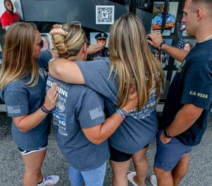 The Freeman family gather to find Russell's picture on the traveling memorial at the Adult Correctional Institutions, part of the National