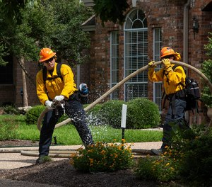 """A firefighter sprays an area labeled """"fire"""" during a simulated wildfire exercise in the Jester Estates neighborhood inWest Austinon Tuesday. The program is one of the first in the country to focus on urban interface firefighting."""