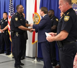Gov. Ron DeSantis hands out one-time relief checks to first responders at the Jacksonville Sheriff's Office on Aug. 10, 2021.