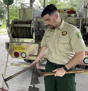 Peter Scalco, a Florida Forest Service wildfire firefighter, holds up the hand tools he used to cut lines around a 35,000-acre fire in Montana.