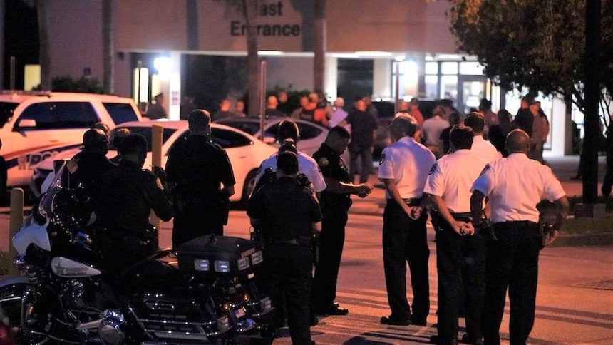 Police stand at attention as the alert tone comes over the radio at Halifax Health that Daytona Beach Police officer Jason Raynor had passed away onTuesday, Aug. 17, 2021.