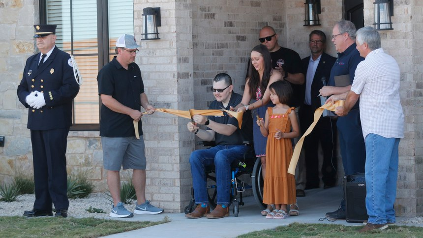 Lubbock Fire Rescue Firefighter Matt Dawson and wife, Chanda, and his 7-year-old daughter, Preslee, cut the ribbon to their new home. He and his family were presented a new home onRichmond Avenue.