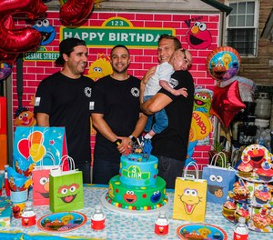 From left: Firefighters Manuel Costa, Lawrence Young, and Steve Keenan, holding Liam Dominguez Rodriguez during the boy's birthday party.