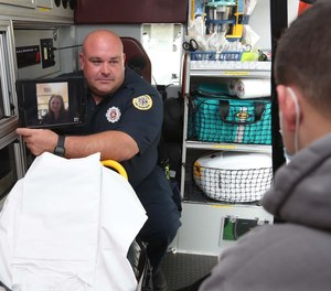 Firefighter/paramedic Adam Lovell, left, holds a tablet showing Dr. Holli Hill via the Akron Fire Department's new telehealth program during a demonstration with firefighter/paramedic Dan Hilton portraying the patient Tuesday, Sept. 14, 2021 in Akron, Ohio.