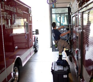 A firefighter prepares to go out on a call at Tualatin Valley Fire and Rescue's Newberg, Ore.