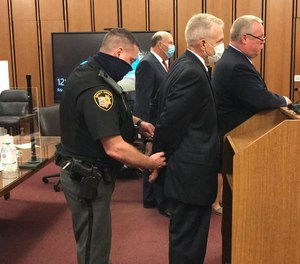 Ex-Cuyahoga County Jail Director Ken Mills is handcuffed after a judge sentenced him to nine months in jail.